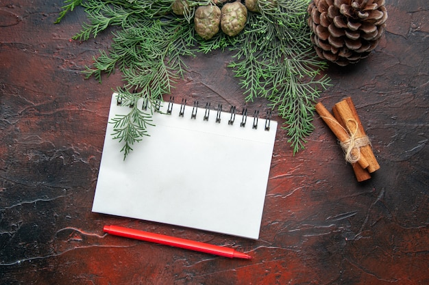 Fir branches and closed spiral notebook with pen cinnamon limes conifer cone on dark background