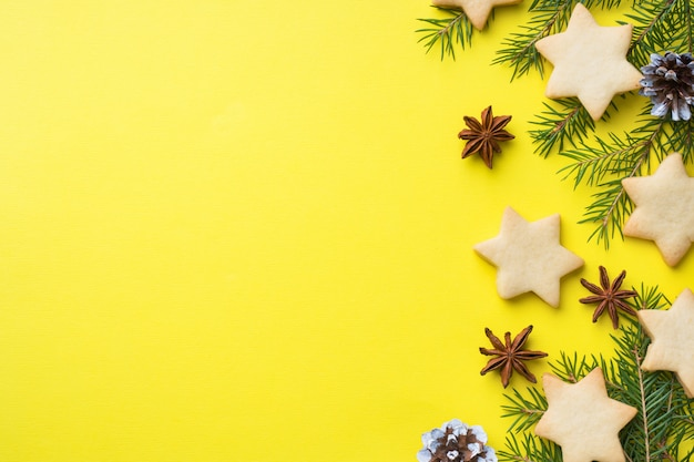 Fir branches, cookies and marshmallows on yellow