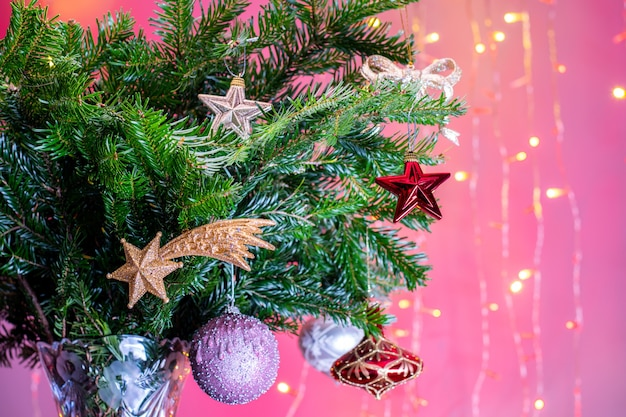 Fir branches decorated for christmas or new year celebration with fairy lights at the background.