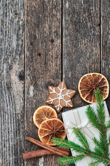 Fir branches, dried oranges, gift, ginger biscuit, cinnamon on wooden.