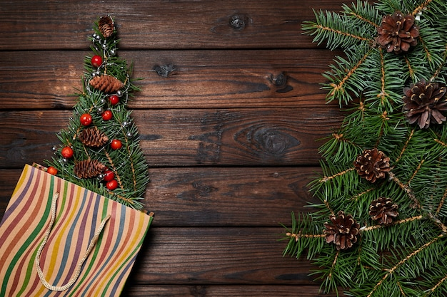 Fir branches in the form of a christmas tree in a paper bag on a wooden background with copy space