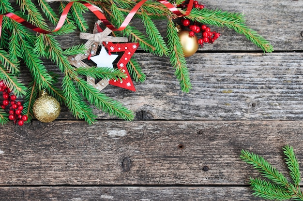 Fir branches, holly berries, decoration on rustic wooden.