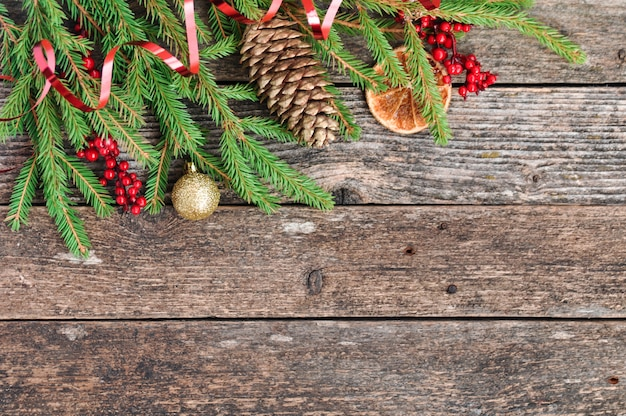 Fir branches, holly berries, dried oranges on rustic wooden.