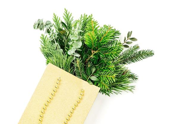 白い背景の上の買い物袋のモミの枝。クリスマスの買い物のコンセプト。フラットレイ、上面図