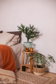 花瓶のモミの枝とベッドのそばの木製テーブルのクリスマスの装飾