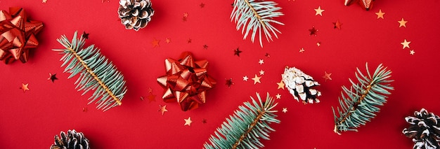 Fir branches, pine cones and festive confetti on red background, top view