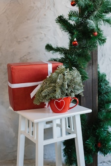 Fir branches in a red vase mug and a red gift box on a table in the living room