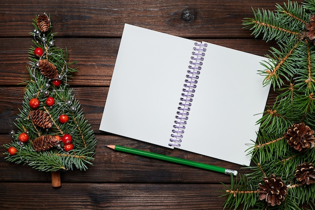 Fir branches in the shape of a christmas tree and a blank notepad on a wooden background