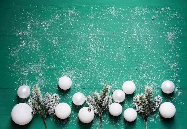Еловые ветки белые новогодние шары лежат на зеленом деревянном фоне, покрытом снегом