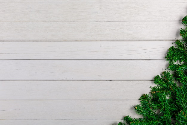 Fir branches on white wooden board background