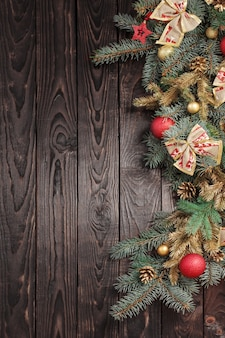 Fir branches with christmas decor on old dark wooden wall