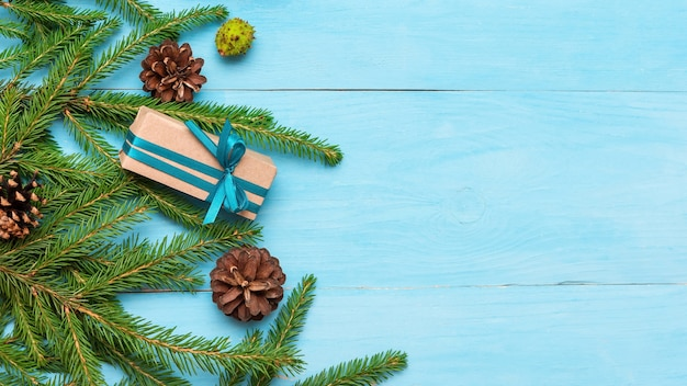 Fir branches with cones on a light blue background and gifts with copy space.