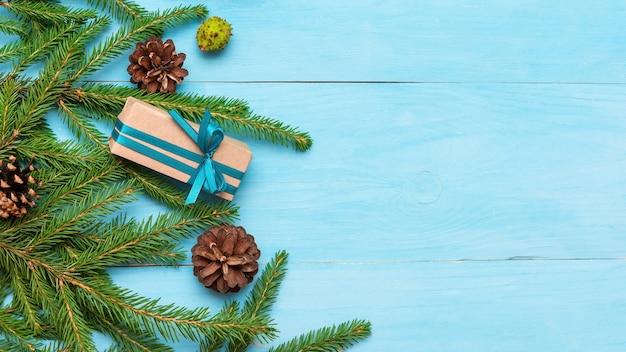 Еловые ветки с шишками на голубом фоне и подарки с копией пространства.