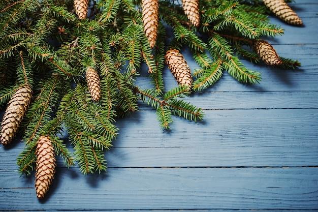 Еловые ветки с шишками на синем деревянном фоне