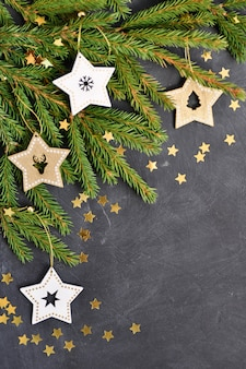 The fir branches, wooden star decoration, gold confetti on dark