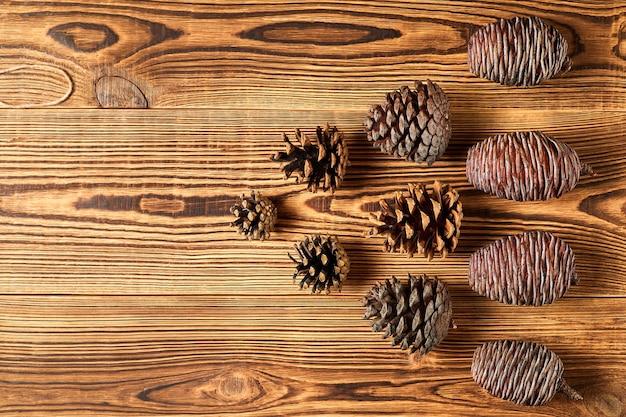 Еловые шишки на коричневом деревянном фоне с копией пространства