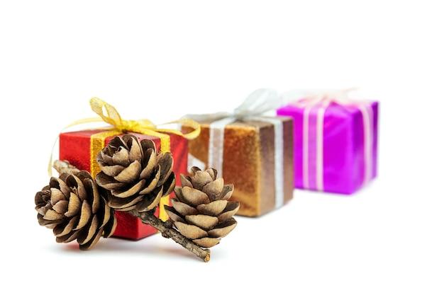 흰색으로 격리된 크리스마스 또는 새해 디자인을 위한 선물 상자가 있는 전나무 콘