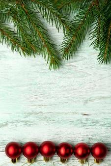 rami di conifere di pino abete rosso abete scintillanti lucenti palline colorate multicolori su un legno marrone opaco