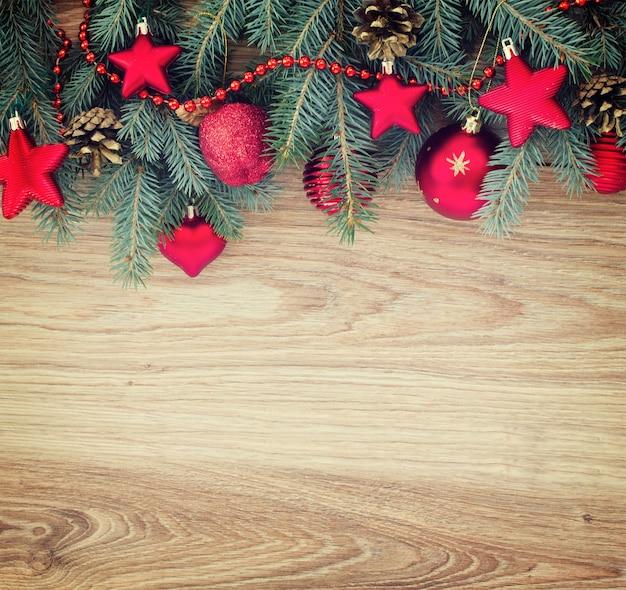 복사 공간이 있는 나무 배경에 빨간색 크리스마스 장식이 있는 전나무 테두리, 복고풍 톤