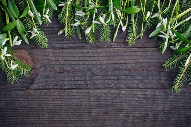 暗い木のテーブルの上のモミの木の枝とスノードロップ。