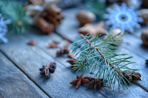 Fir tree branch and anise stars on wooden table, close up view