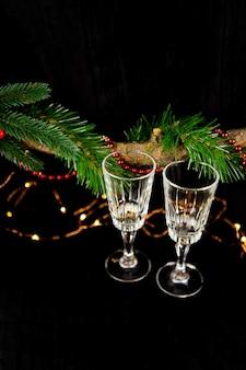 クリスマスライトとシャンパングラスで飾られたモミの木の枝