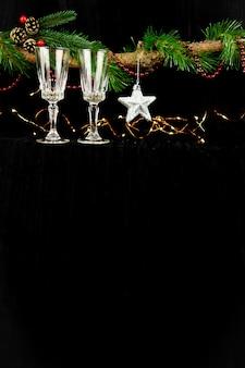 クリスマスライト、シルバースター、シャンパングラスで飾られたモミの木の枝