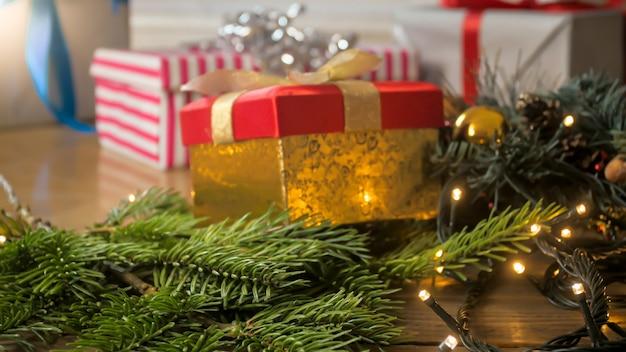 Еловая ветка, украшенная светящимися огнями, лежит на полу рядом с рождественскими подарочными коробками