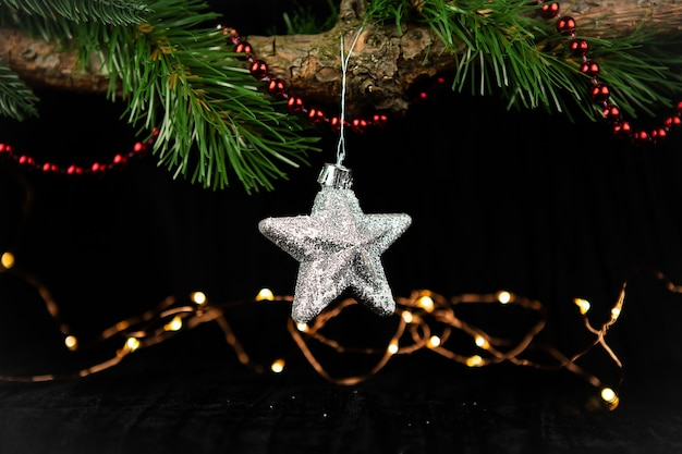 光沢のあるシルバースターとクリスマスライトで飾られたモミの木の枝