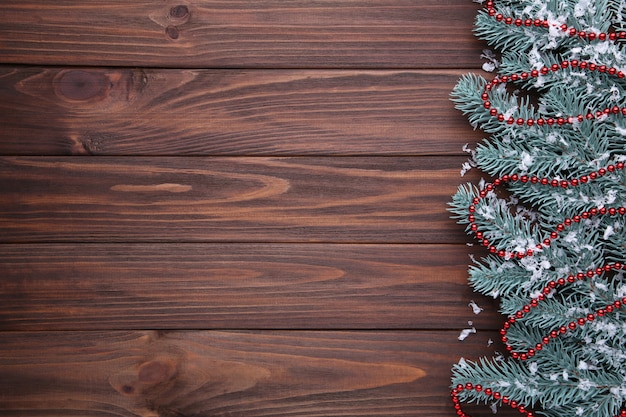 Fir-tree branch with beads on brown background