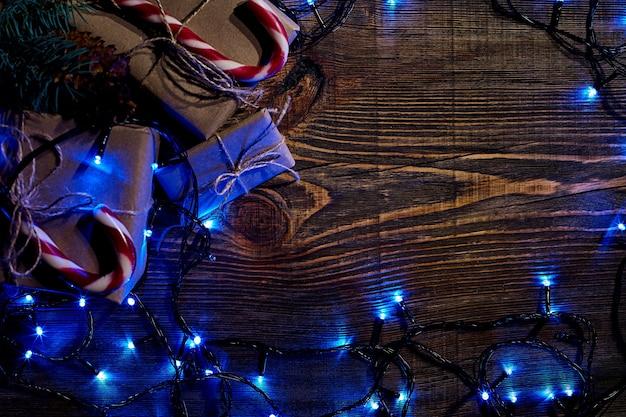 크리스마스 조명 선물 상자가 있는 전나무 가지와 복사 공간이 있는 나무 배경에 사탕 지팡이