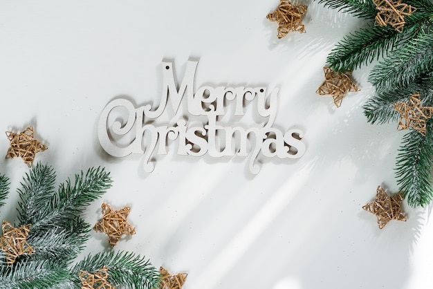 Fir tree branch with gold wooden stars and letters merry christmas on white paper, top view copyspace