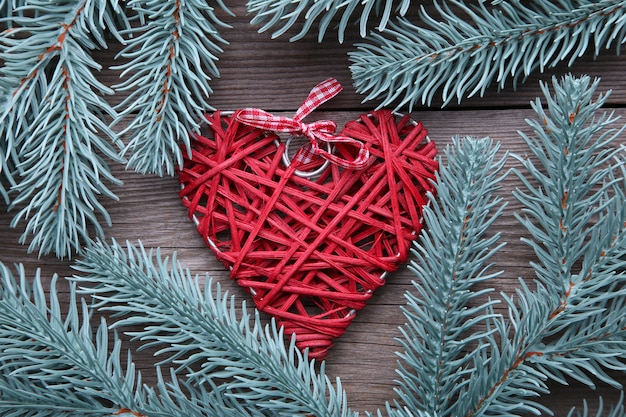 Fir tree branch with a red heart on a grey background.