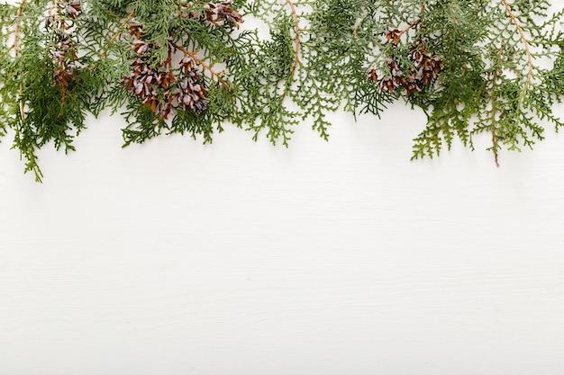 Еловые ветви, шишки новогодняя рамка на белом деревянном фоне. рождественский фон с копией пространства