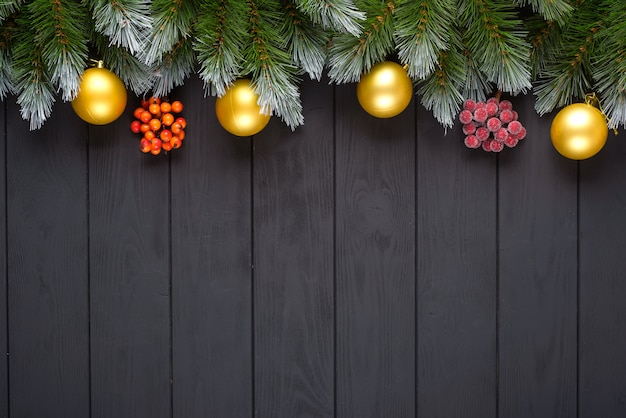 Fir-tree branches, colorful balls, candy cane on black background