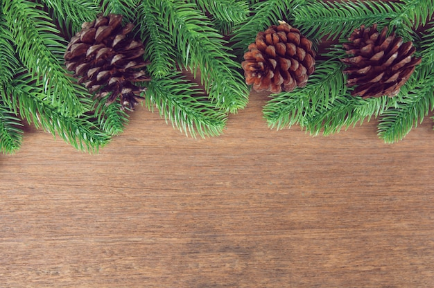 Fir tree branches and pine cones with decoration on a wooden board