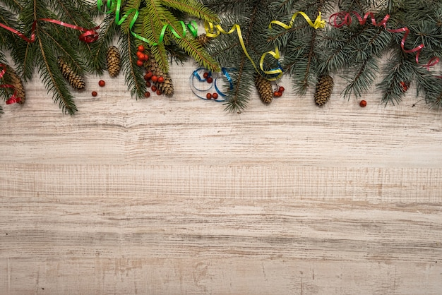 Fir tree branches with cones on wooden table. christmas and new year postcard