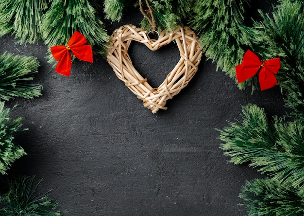 Fir tree branches with wooden heart on black