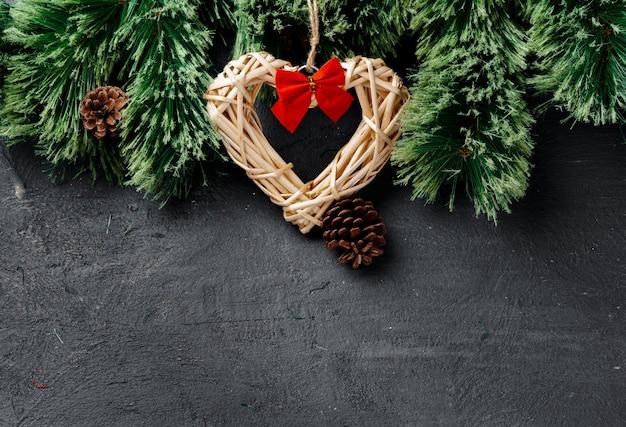 Еловые ветки с деревянным сердцем на черном