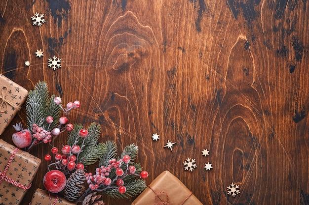 전나무 장식 빨강 및 녹색 크리스마스 공, 모양의 계피 및 마른 오렌지 조각이 크리스마스 인사말을 위해 나무 배경에 있습니다. 복사 공간이 있는 상위 뷰입니다. 크리스마스 인사말 카드입니다.