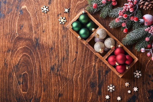 モミの木の装飾の赤と緑のクリスマスボール、形をしたシナモンとドライオレンジのスライスを木の背景にクリスマスの挨拶に。コピースペースのある上面図。クリスマスのグリーティングカード。