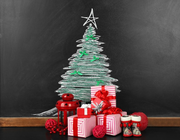 Fir tree drawing on blackboard and beautiful gifts. xmas background