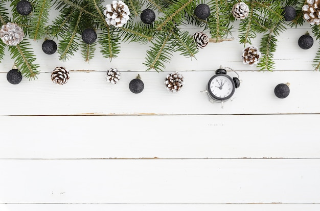 Fir tree pine cones,  black balls, alarm clock on wooden christmas background.flat lay fra