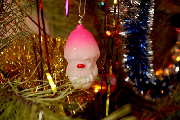The fir-tree toy the gnome in a pink cap attached by a paper clip on a fir-tree branch