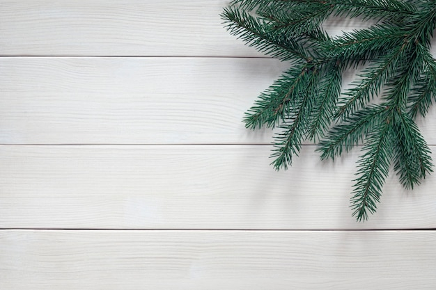 Fir tree twigs without ornaments on white wooden background