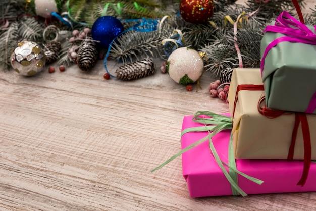 木製のテーブルにギフトボックスとモミの木。クリスマスプレゼントのコンセプト、ポストカード、挨拶