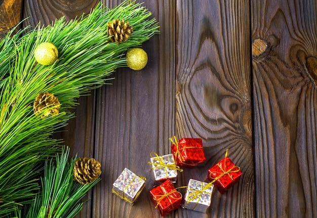 Елка с игрушками и подарками на коричневом деревянном фоне