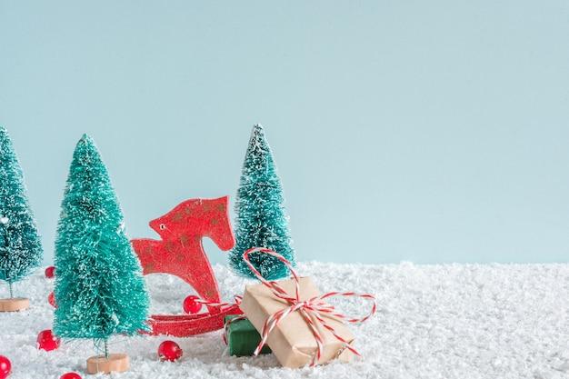 雪の背景に馬のおもちゃ、ギフトボックス、赤い果実とモミの木