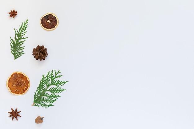 전나무 나뭇 가지와 스타 아니스, 흰색 배경에 마른 감귤류와 나무 콘, 크리스마스 휴일 배경, 평면 평신도, 복사 공간