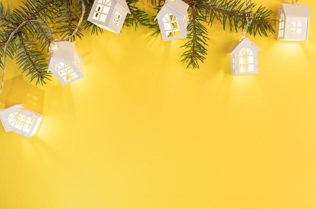 Ветки ели с игрушками дома на желтом фоне. вид сверху.